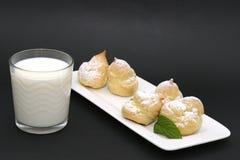 Frukosten mjölkar och eclairkakan på en svart bakgrund royaltyfria foton