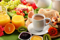 Frukosten tjänade som med kaffe, orange fruktsaft, ägget och frukter Arkivfoto