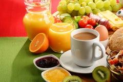 Frukosten tjänade som med kaffe, orange fruktsaft, ägget och frukter Arkivbilder