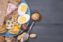 Frukostera bakgrund med muttrar, ägget, bröd på ett träbräde Royaltyfria Foton