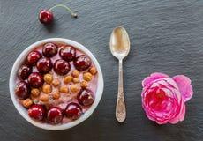 Frukostera bunken med yoghurt, granola eller mysli eller havreflingor, nya körsbär och muttrar Svart stenbakgrund, rosa färgrosbl Royaltyfri Foto
