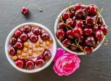 Frukostera bunken med yoghurt, granola eller mysli eller havreflingor, nya körsbär och muttrar Svart stenbakgrund, rosa färgrosbl Royaltyfri Bild