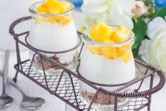 Frukostera efterrätten med kliflingor, den vanliga yoghurten och mango, closeup Arkivfoton