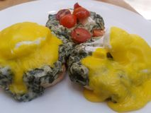 Frukostera engelska muffin som täckas i lagad mat med grädde spenat tjuvjagad ägg och hollandaisesås Royaltyfri Foto