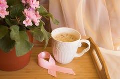 Frukostera för kvinnor - rosa bröstcancer för bandmedvetenhetsymbol Kaffekopp på ett trämagasin och en rosa violet Fotografering för Bildbyråer