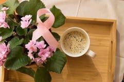 Frukostera för kvinnor - rosa bröstcancer för bandmedvetenhetsymbol Kaffekopp på ett trämagasin och en rosa violet Royaltyfri Foto