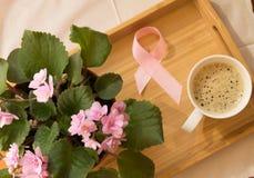 Frukostera för kvinnor - rosa bröstcancer för bandmedvetenhetsymbol Kaffekopp på ett trämagasin och en rosa violet Arkivbild