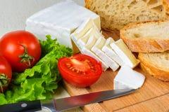 Frukostera från bröd, ost, tomater och över hela sallad på en trätabell Royaltyfri Bild