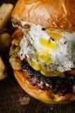 Frukostera hamburgaren med ett stekt ägg på mörk lantlig yttersida Royaltyfri Fotografi