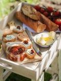 Frukostera i en trädgård med spridning för nytt bröd, för körsbärsröda tomater, smör- och ost Arkivbilder