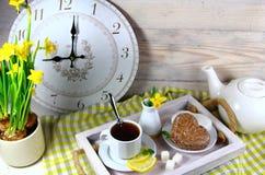Frukostera i säng med en kopp te med citronen Arkivfoton