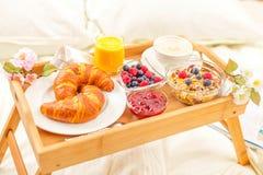 Frukostera i säng med frukter och bakelser på ett magasin arkivbilder