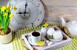 Frukostera i säng med marshmallower, en kopp te med citronen Royaltyfri Foto