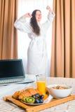 Frukostera i säng och sträcker sig en kvinna Royaltyfri Foto