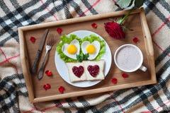 Frukostera i säng med hjärta-format ägg, rostade bröd, driftstopp, kaffe, rosa och kronblad Valentindagöverraskning Arkivbilder