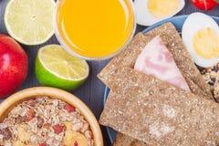 Frukostera inklusive det kokta ägget, äpplet, orange fruktsaft, mysli Royaltyfri Foto