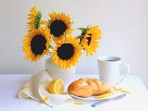 Frukostera kaffe med nytt bröd och citronen på den vita bordduken med härliga solrosor i den vita vasen. Arkivfoton