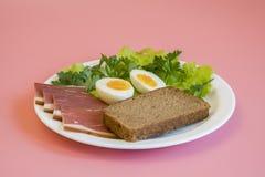 frukostera kokta ägg, bacon, gräsplaner i en vit platta på rosa bakgrund Fotografering för Bildbyråer