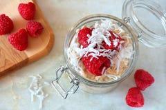 Frukostera kylskåphavremjölet med den nya hallon och kokosnöten Arkivfoton
