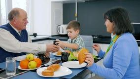Frukostera lyckligt pensionärfolk, morföräldrar med sonsonen äter den aptitretande bullen stock video