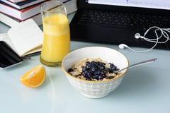 Frukostera med bär och orange fruktsaft, bärbara datorn, telefon Royaltyfri Bild