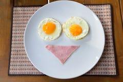 Frukostera med bacon och stekte ägg på den vita plattan Arkivfoto