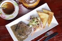 Frukostera med beafsteak, bröd, grönsaken och te Royaltyfria Foton