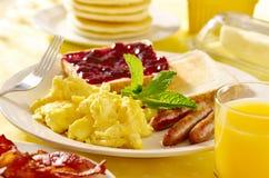 Frukostera med förvanskade ägg, korvsammanlänkningar och t Royaltyfria Bilder