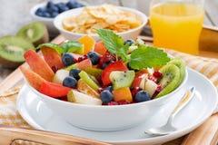 Frukostera med fruktsallad, cornflakes och orange fruktsaft Royaltyfria Bilder