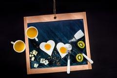 Frukostera med ägg, orange fruktsaft på den svart tavlan Arkivbild