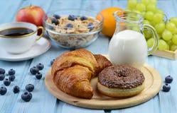Frukostera med gifflet, munken, kaffe, sädesslag och frukter Arkivfoto