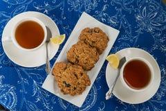 Frukostera med havremjölkakorna och citronteet Arkivfoton