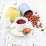 Frukostera med hemlagade kakor, äpplet och muttrar med kopp te Arkivfoton