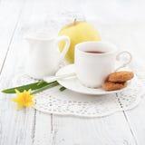 Frukostera med hemlagade kakor och äpplet, med kopp te Arkivbild