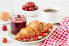 Frukostera med kaffe-, giffel- och jordgubbedriftstopp på en tabell arkivbild