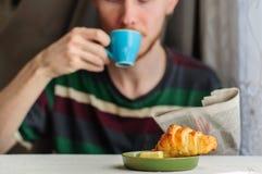 Frukostera med kaffe och gifflet med den unga mannen på bakgrund Royaltyfria Bilder