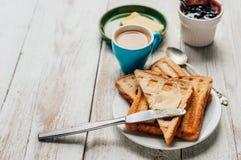 Frukostera med kaffe, rostade bröd, smör och driftstopp Arkivfoton