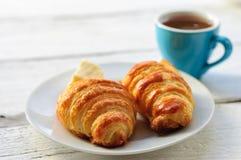 Frukostera med nytt bakat giffel, smör och kaffe Arkivbild