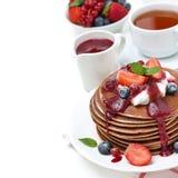 Frukostera med pannkakor med kräm, fruktsås och bär arkivbild