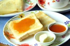 Frukostera med rostat bröd, smör, aprikosdriftstopp, kaffe och pannkakor Slapp fokus Arkivfoton