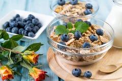 Frukostera med sädesslag, blåbär, mjölka och steg blommor på en träbakgrund Royaltyfri Foto