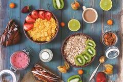 Frukostera med sädesslag, frukter och bär på en blå lantlig bakgrund Sikt från över, framlänges lekmanna- tonat foto fotografering för bildbyråer