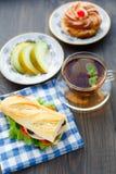 Frukostera med smörgåsen, te, kakan och melon Royaltyfria Bilder
