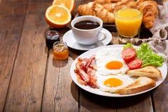 Frukostera med stekte ägg, giffel, fruktsaft, kaffe och frukter Arkivbilder