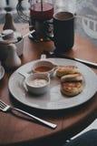 Frukostera med te, kaffe, smörgåsar och ostkakor i ett kafé Royaltyfri Fotografi