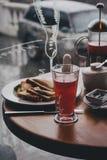 Frukostera med te, kaffe, smörgåsar och ostkakor i ett kafé Arkivfoton