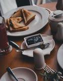 Frukostera med te, kaffe, smörgåsar och ostkakor i ett kafé Arkivbilder