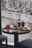 Frukostera med te, kaffe, smörgåsar och ostkakor i ett kafé Arkivfoto