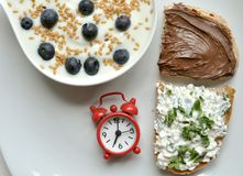 Frukostera med yoghurten, ost, och choklad på vit bordlägger Arkivbilder