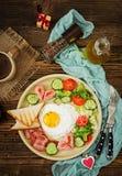 Frukostera på dagen för valentin` s - stekt ägg i formen av en hjärta, rostade bröd, en korv, en bacon och nya grönsaker Arkivbild